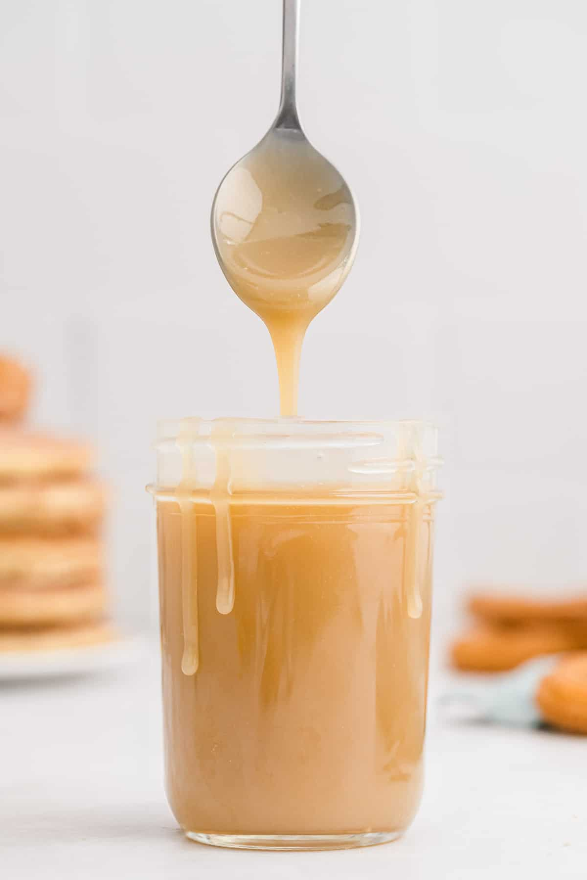 Caramel in a jar, dripping down sides of jar, a spoon hovering over.