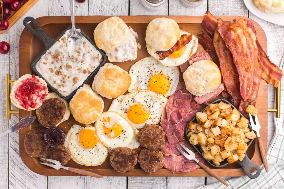 Eggs, bacon, potatoes, biscuits, gravy, jam, and more on large rectangular wooden board.