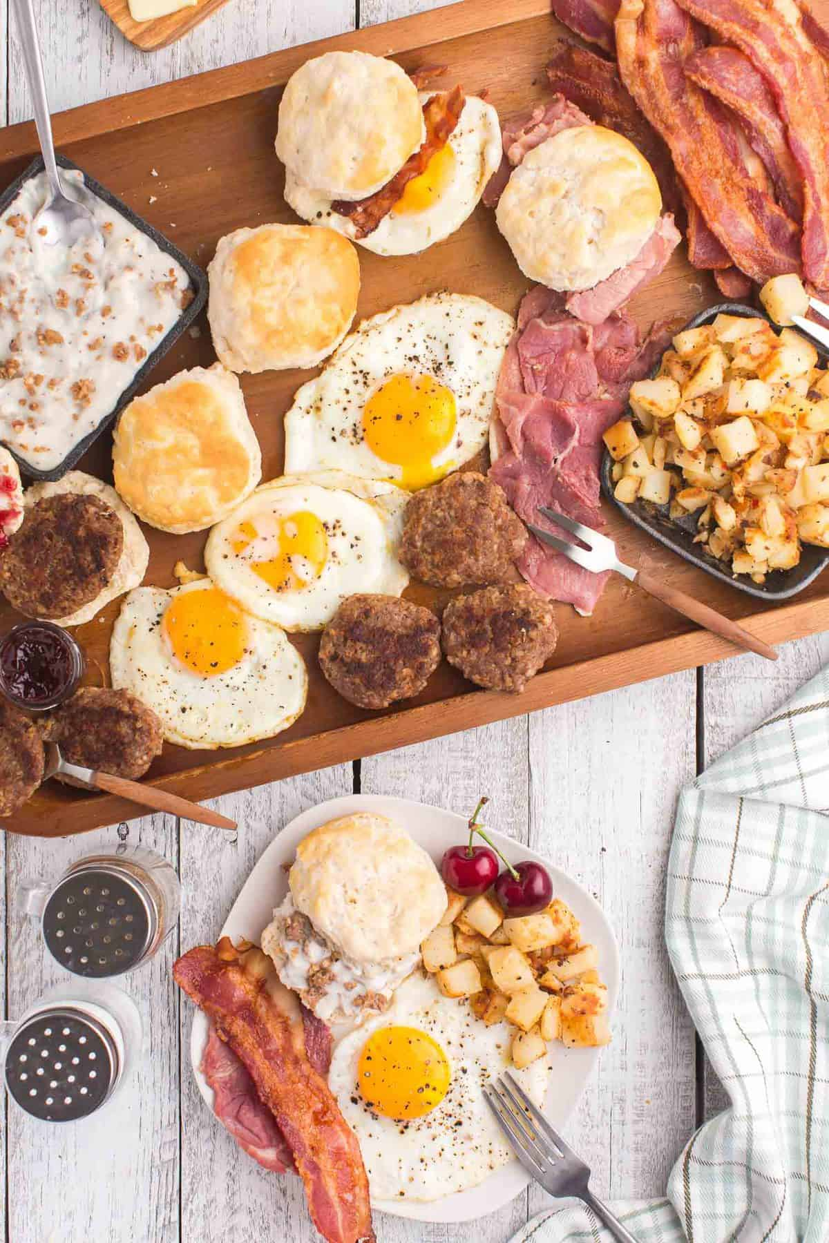 Assorted breakfast items on a wooden tray with a filled plate nearby.