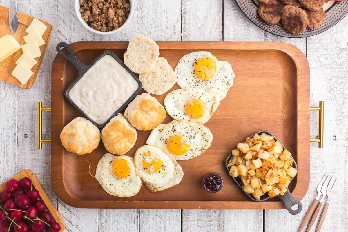 Eggs, biscuits, potatoes and gravy on a wooden tray.