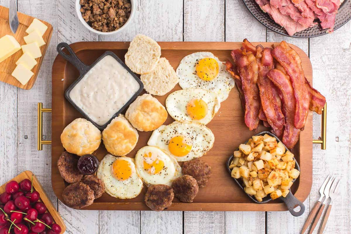 Breakfast board with meat, eggs, and ptoatoes.