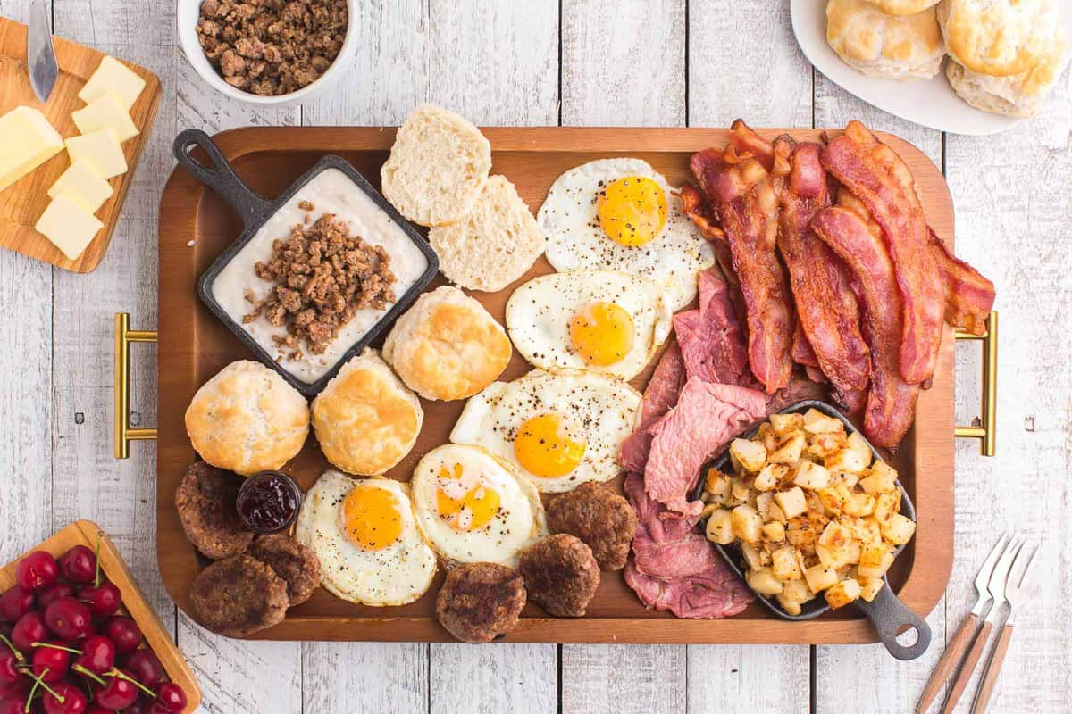 Breakfast board filled with breakfast meats, fried eggs, and cubed potatoes.