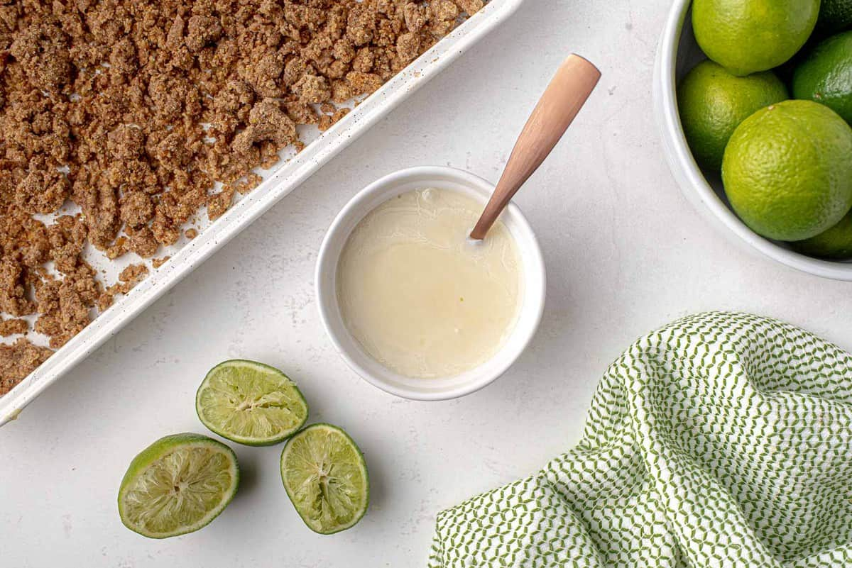Lime syrup in a bowl, limes nearby.