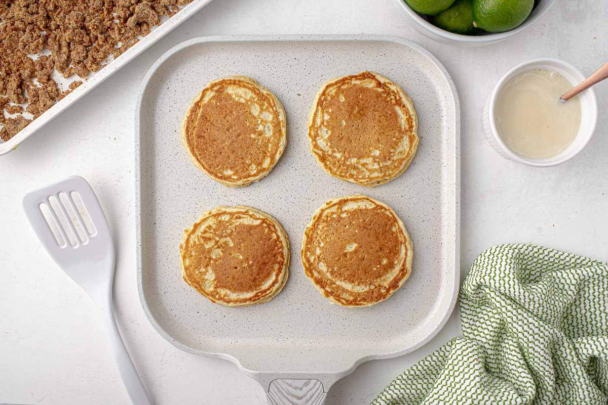 Pancakes on a white griddle.