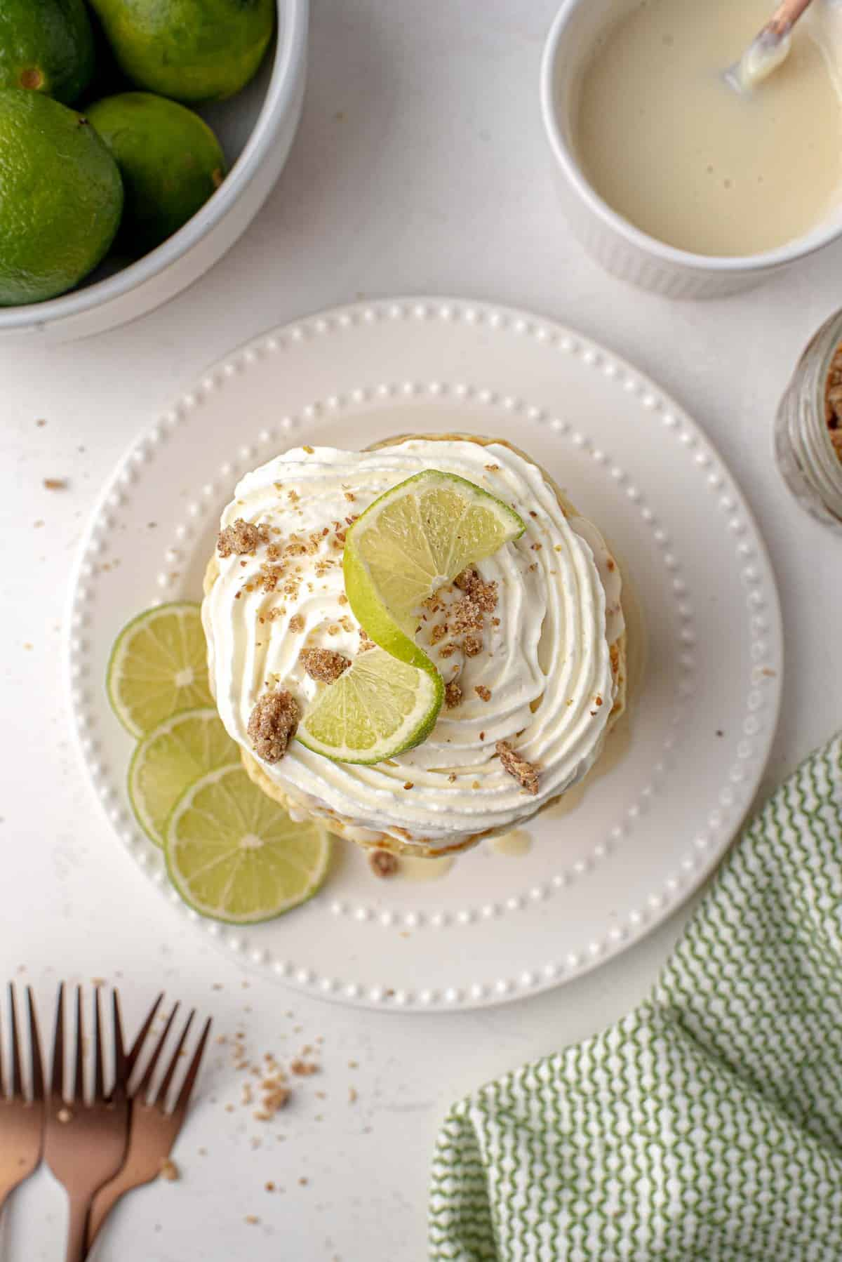 Overhead view of pancakes topped with whipped cream and lime.