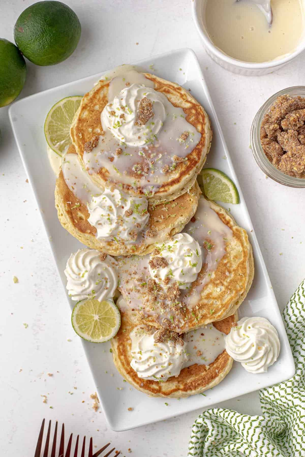Overhead view of four pancakes on a plate with limes, whipped cream, graham cracker crumbs.