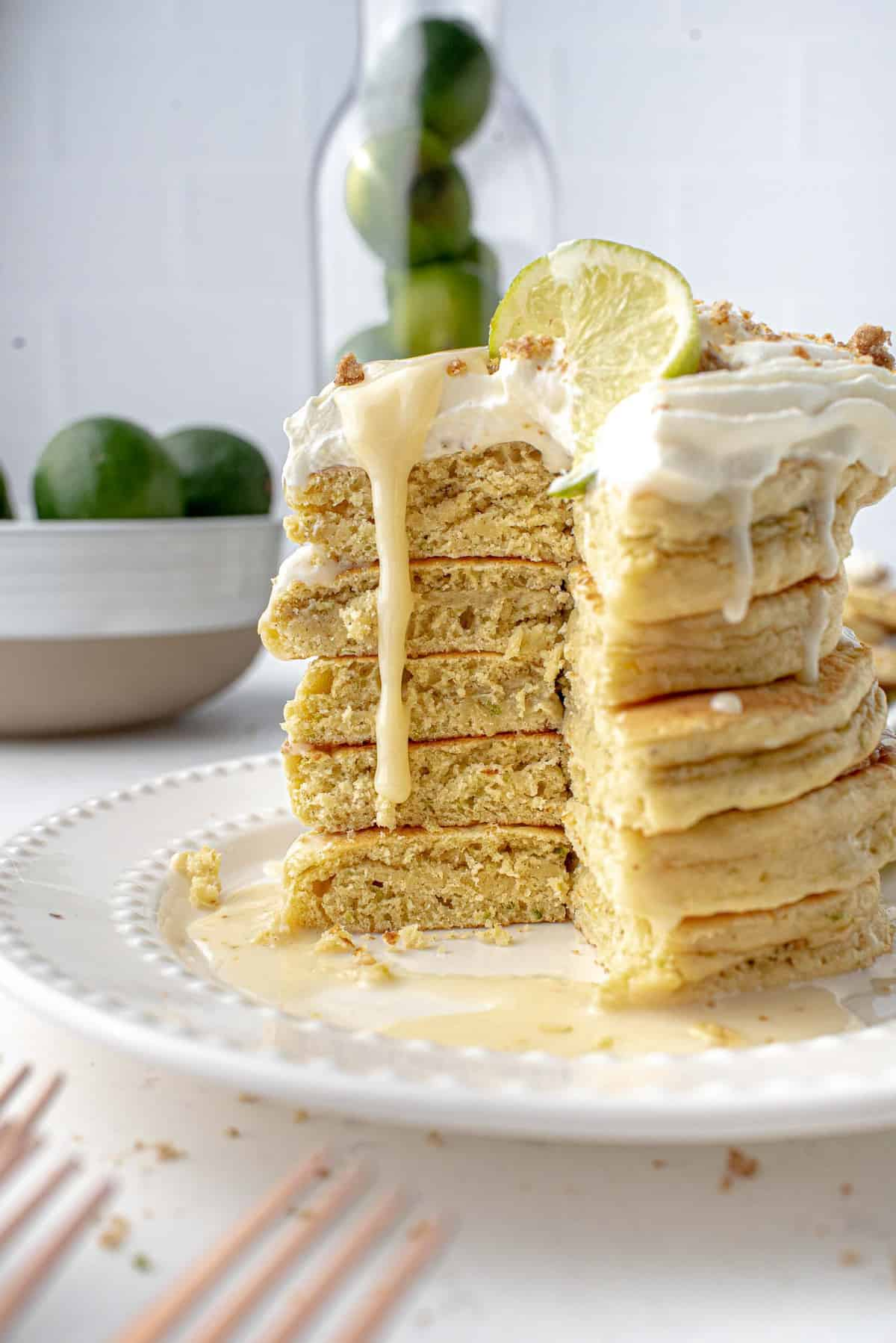 Stack of pancake with lime syrup dripping down cut portion of pancakes.