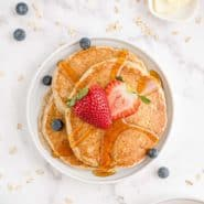 3 pancakes on a white plate, topped with syrup and fresh berries.