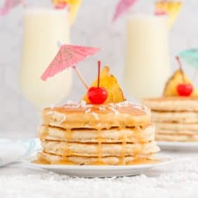 Pineapple pancakes dripping with rum sauce, sprinkled with coconut and topped with a cherry and a paper umbrella.