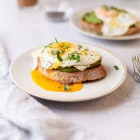 Avocado and runny egg on a slice of toast on a white plate.