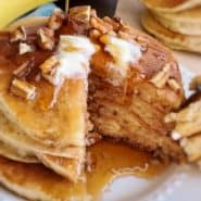 Pancakes topped with butter, walnuts, and syrup.