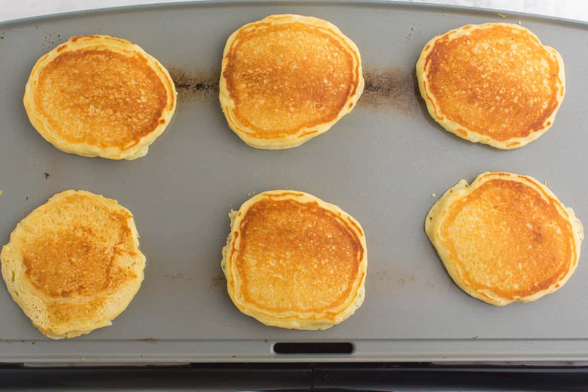 Golden brown cooked pancakes on a griddle.