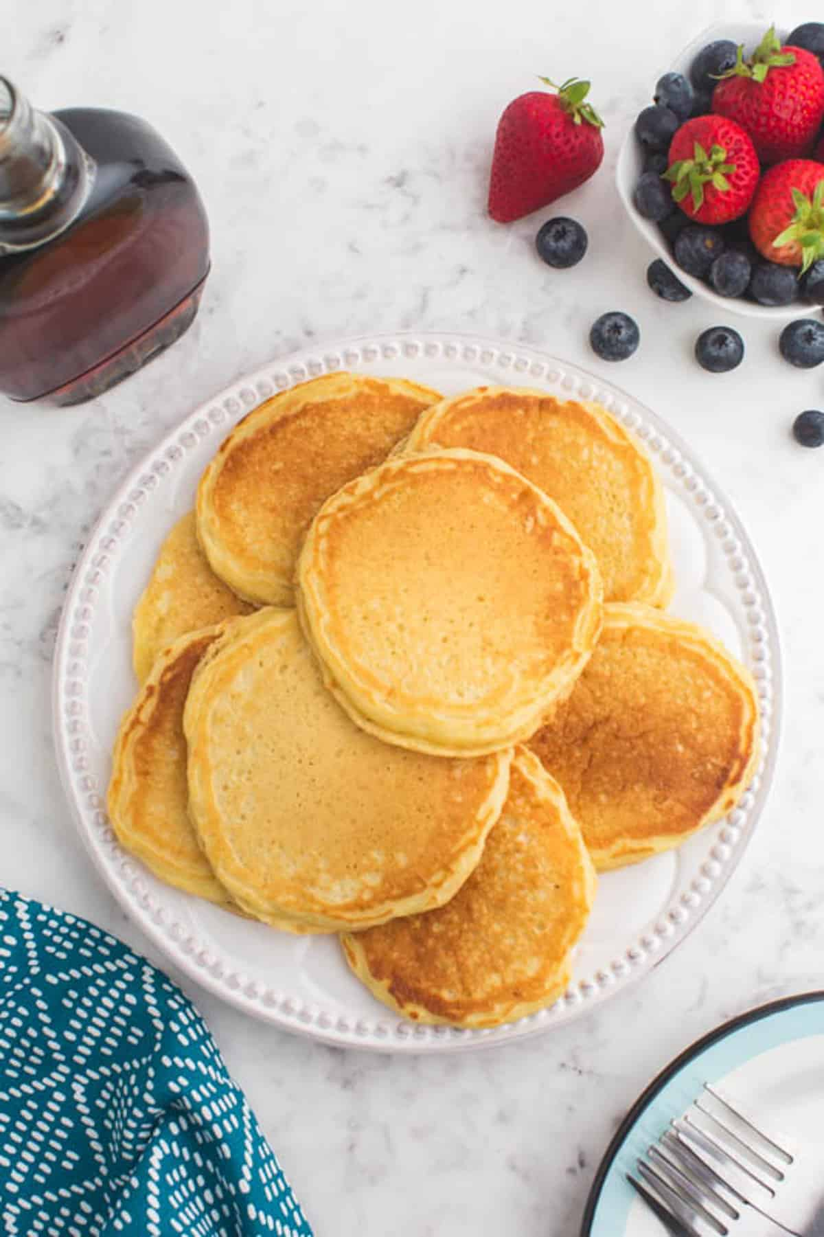 Pile of pancakes on a white plate. Berries and syrup also visible.