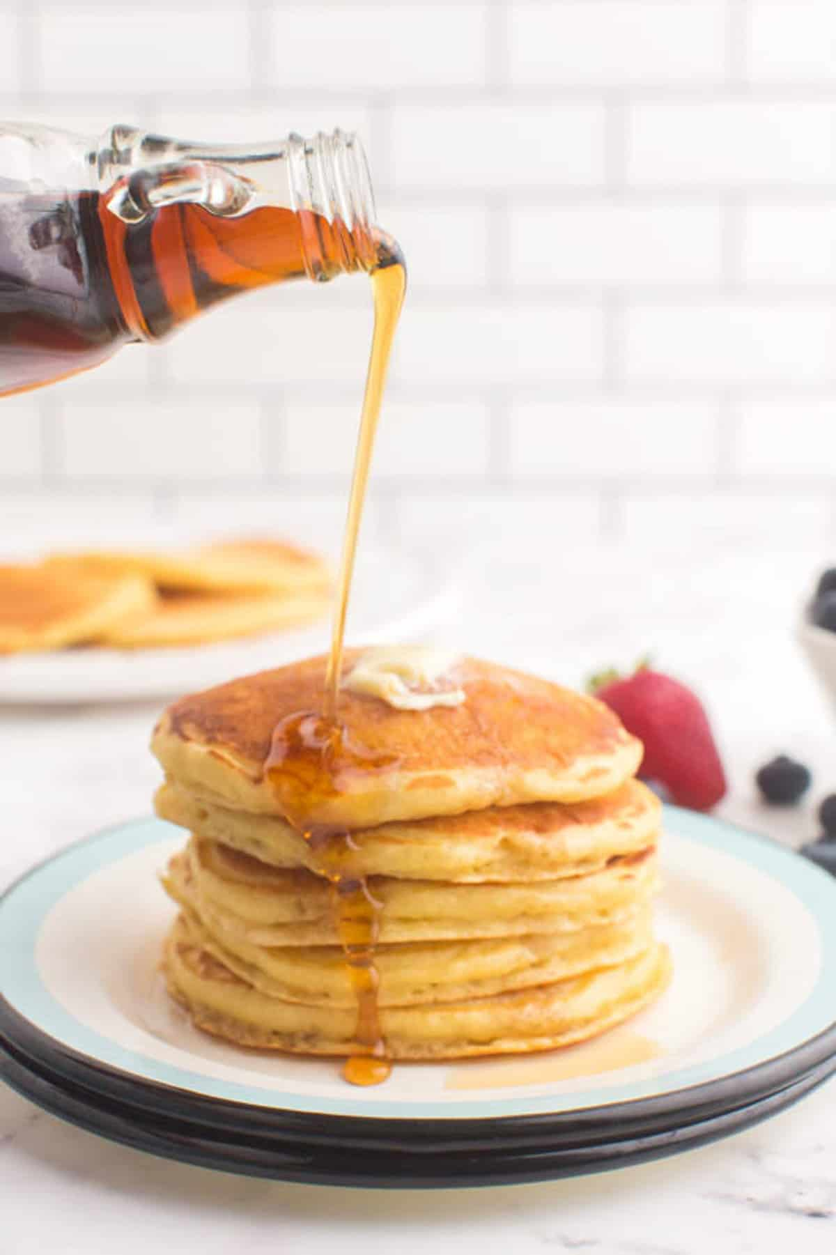 Syrup being poured on a stack of buttermilk pancakes, fresh fruit also visible.
