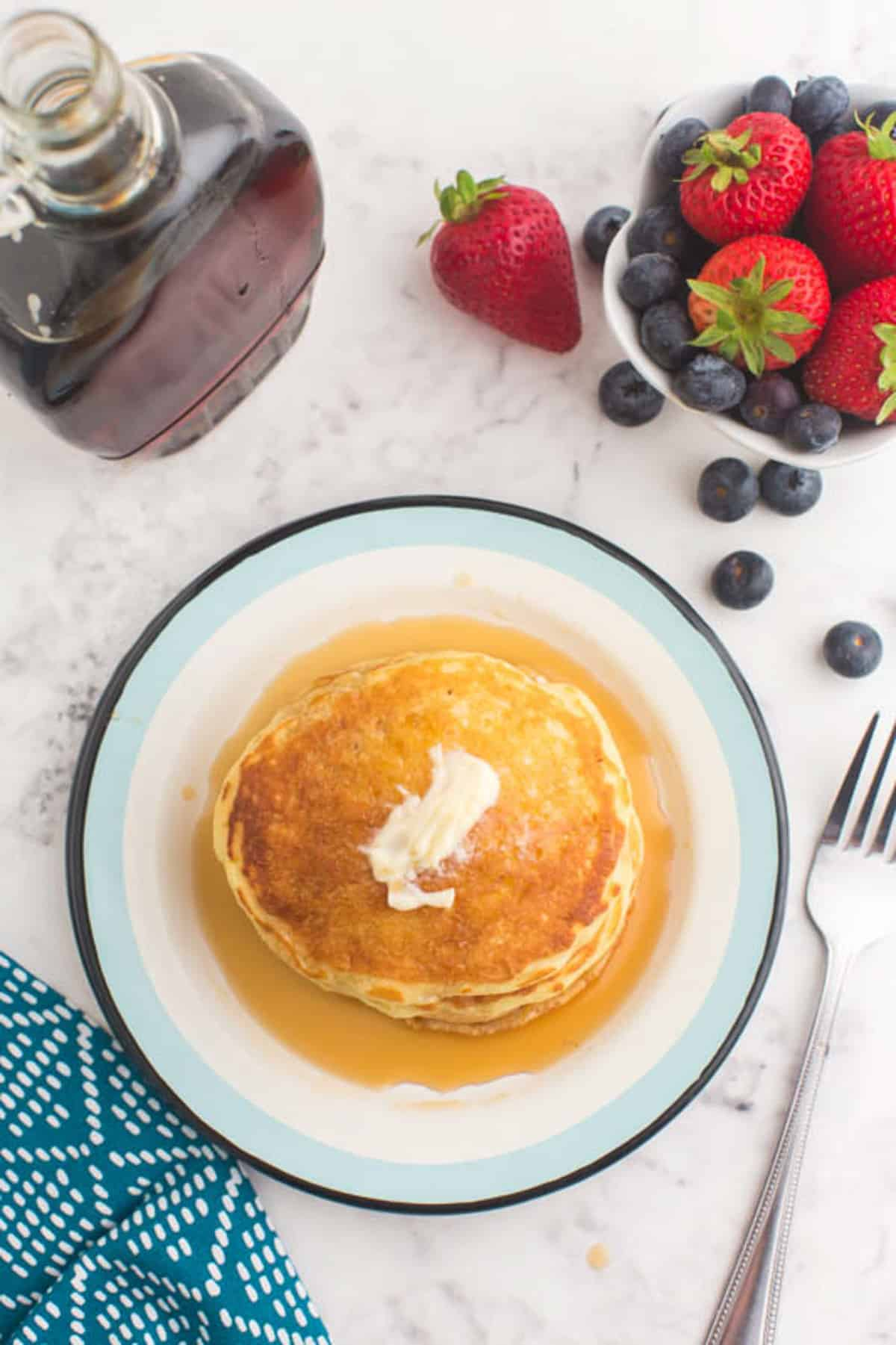 Overhead view of buttermilk pancakes with butter and syrup on a plate.