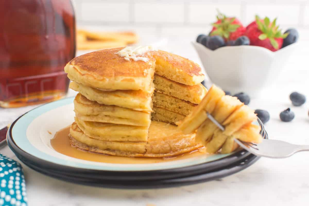 Stack of pancakes on a plate, with a wedge removed on a fork.