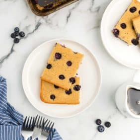 Overhead view of two square blueberry pancakes on a white plate.