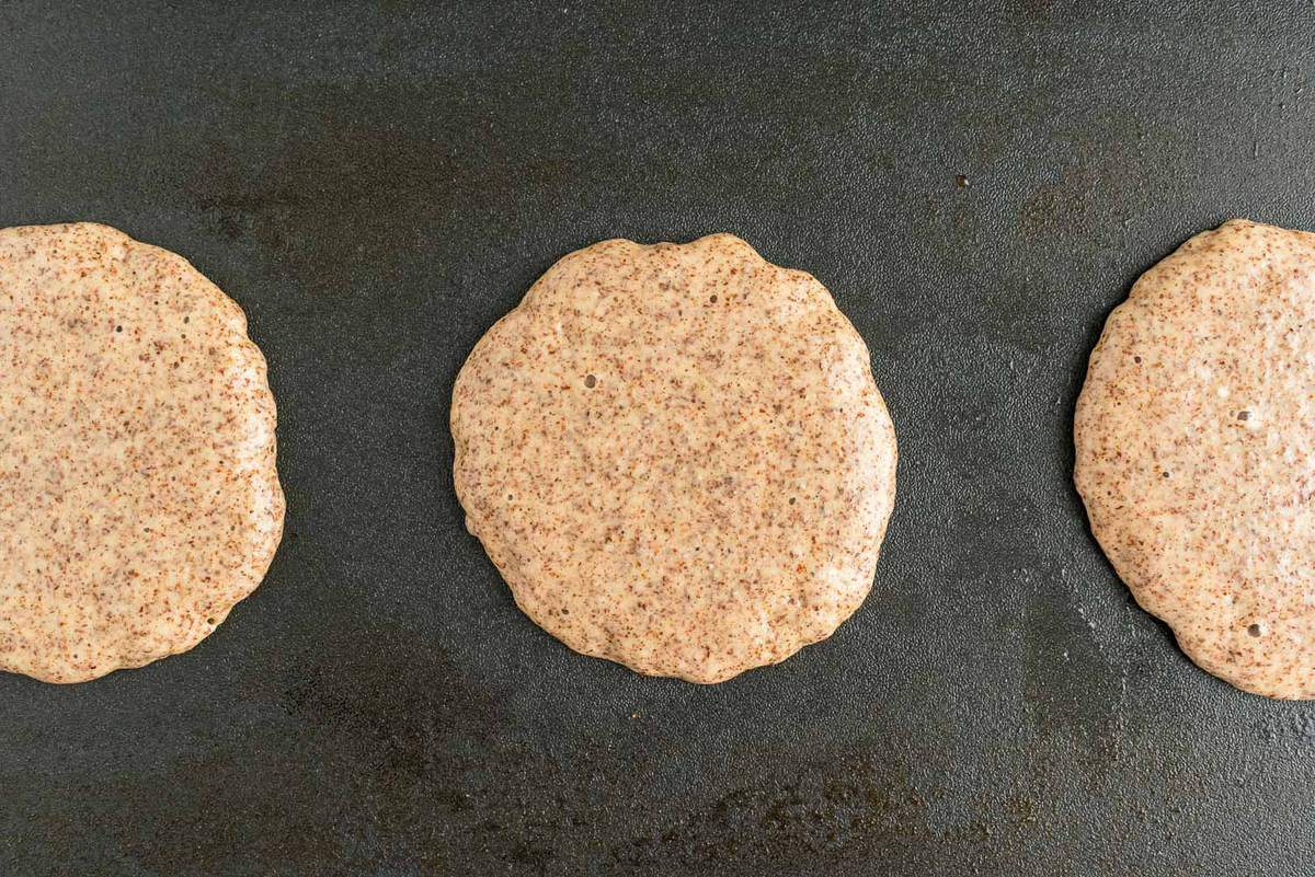 Light brown pancakes on a griddle.