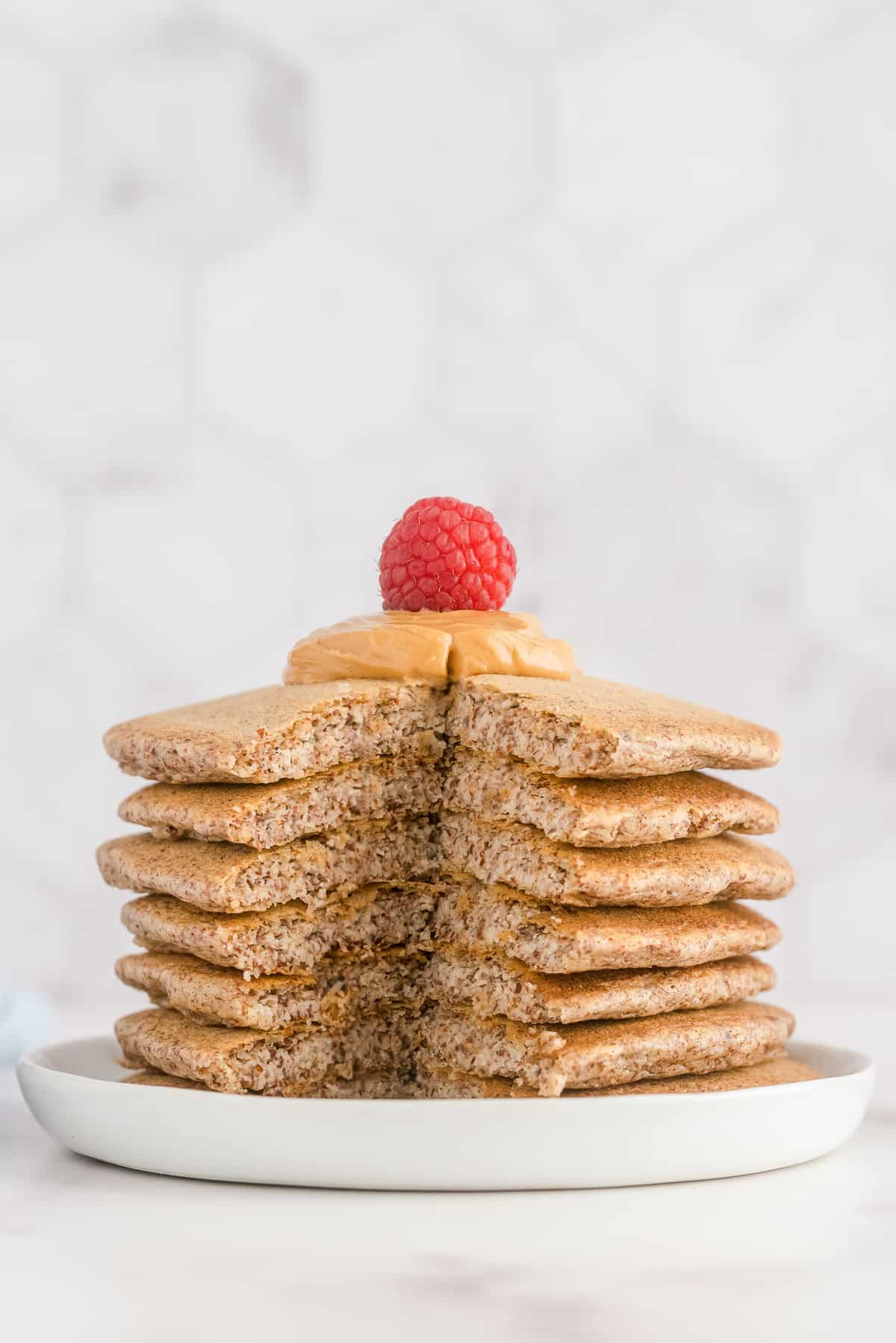 Pancakes stacked up with a cut out of them, on a white plate.