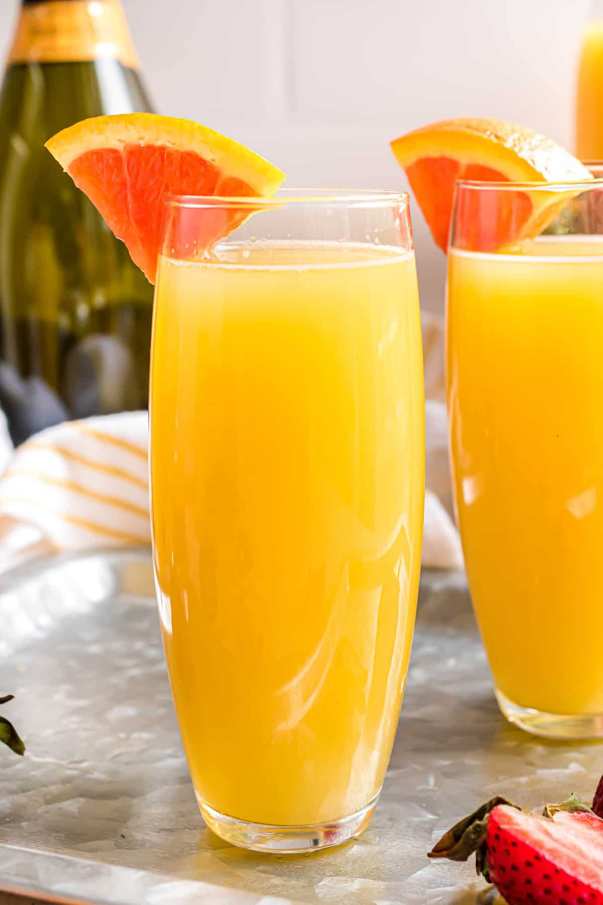 Orange mimosa in a stemless glass garnished with orange wedge.