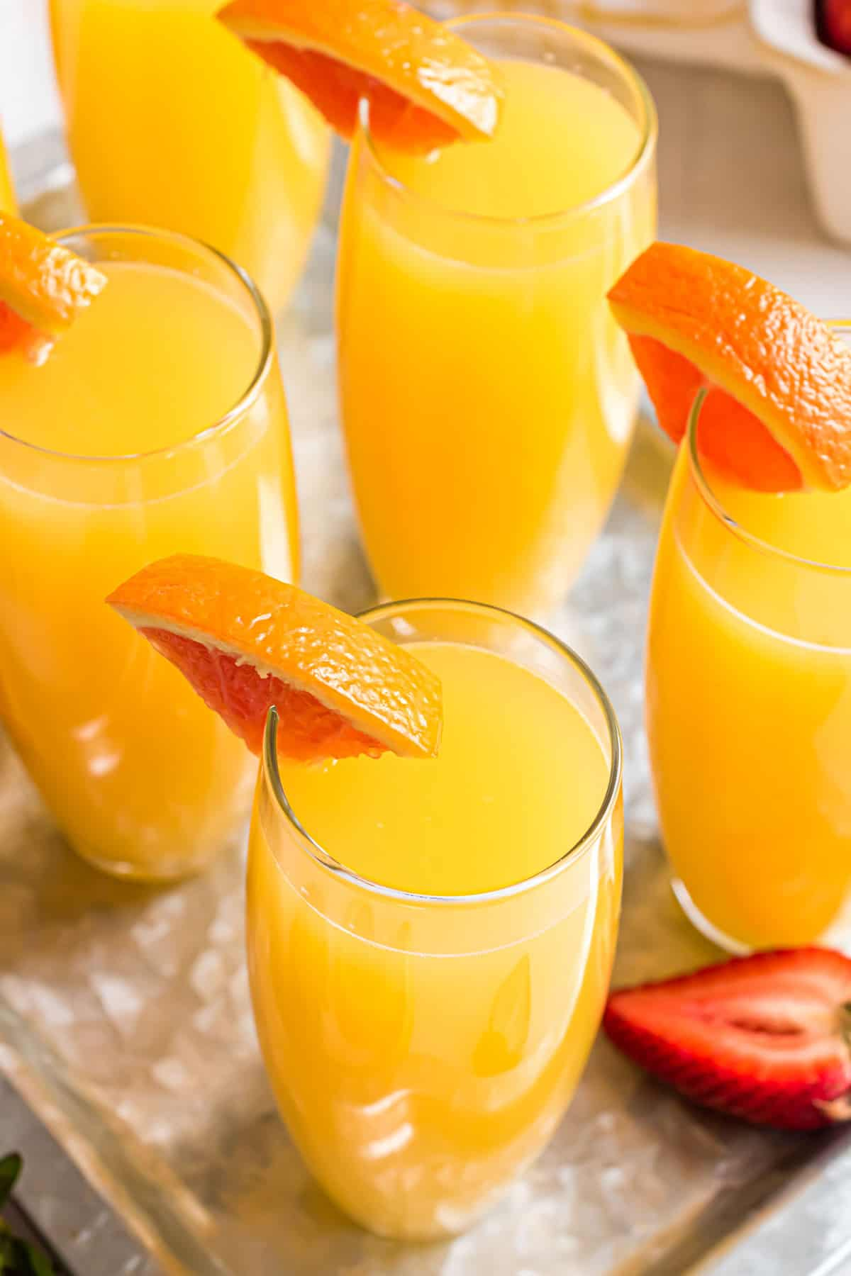 Angled overhead view of mimosas garnished with orange slices.