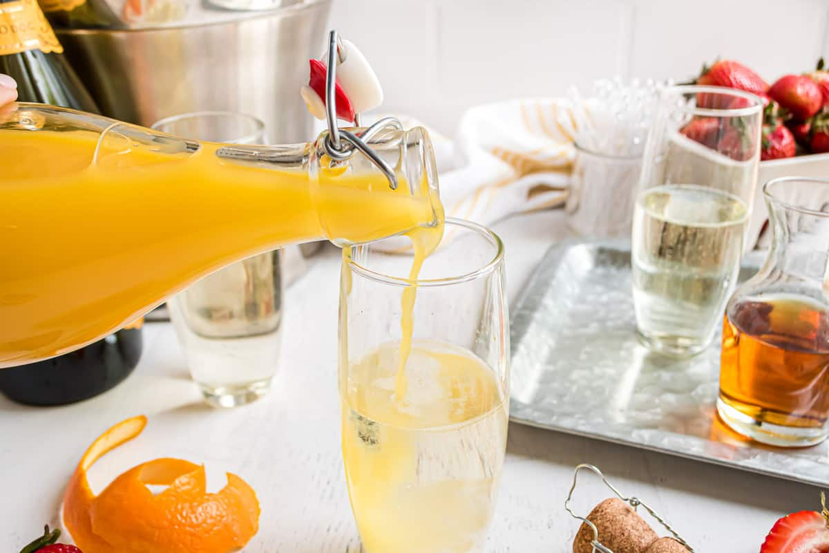 Orange juice being poured into a glass with prosecco.