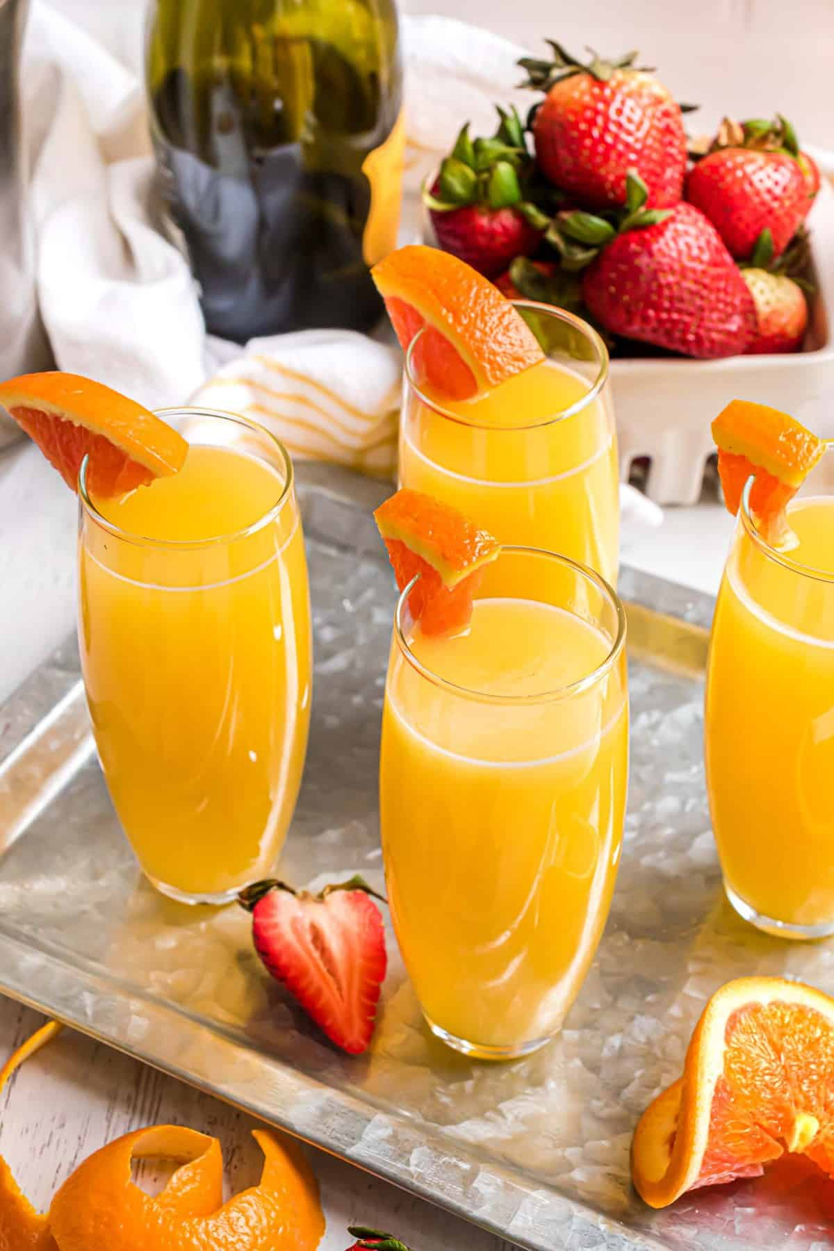 Tray of mimosa cocktails with orange juice and an orange wedge garnish.