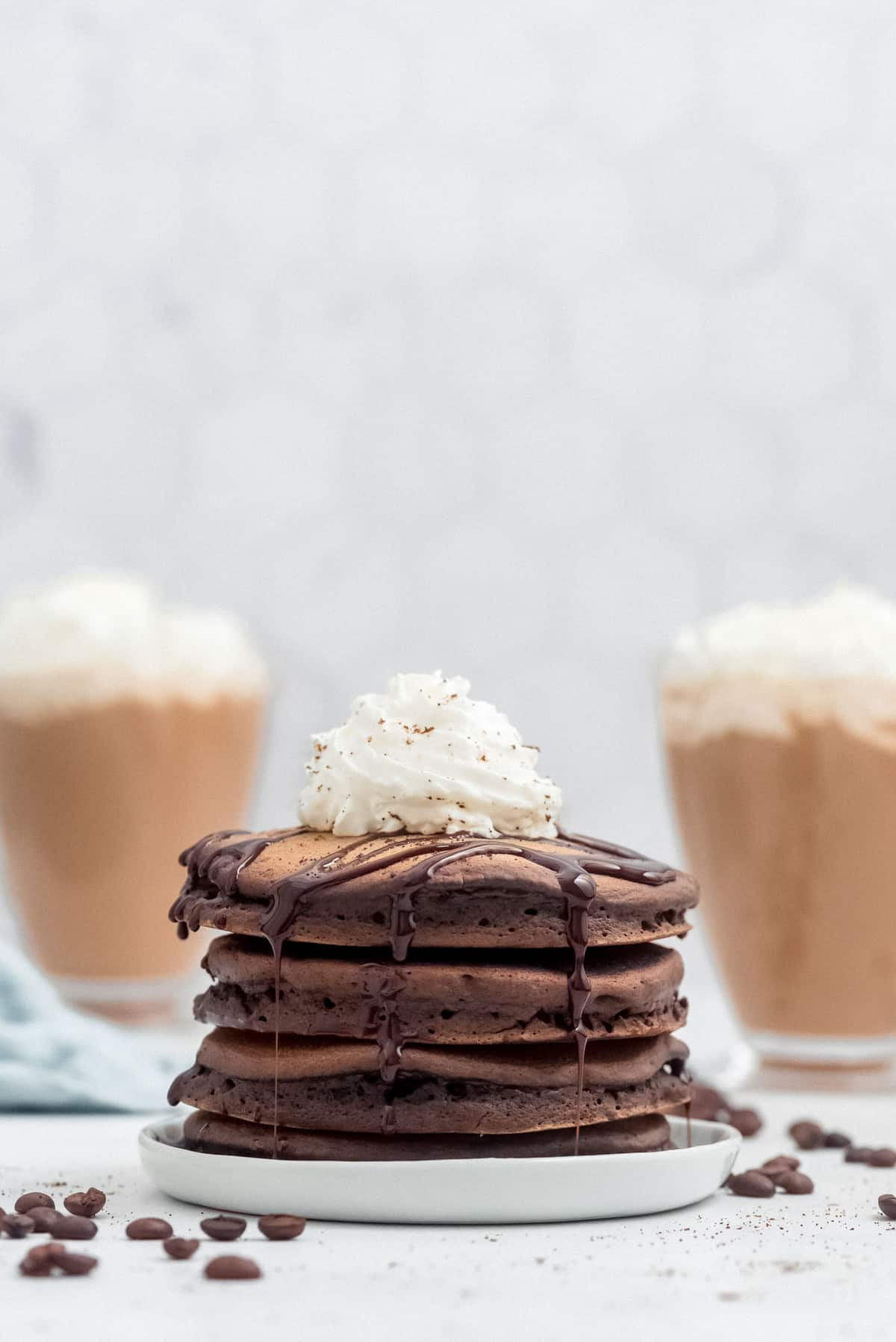 Stack of mocha pancakes with whipped cream, mochas in the background.