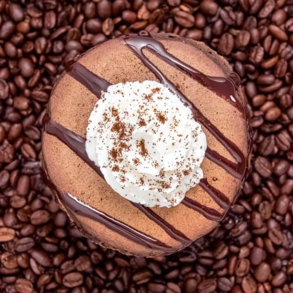 Chocolate pancakes, topped with whipped cream and drizzled with chocolate, on top of coffee beans.