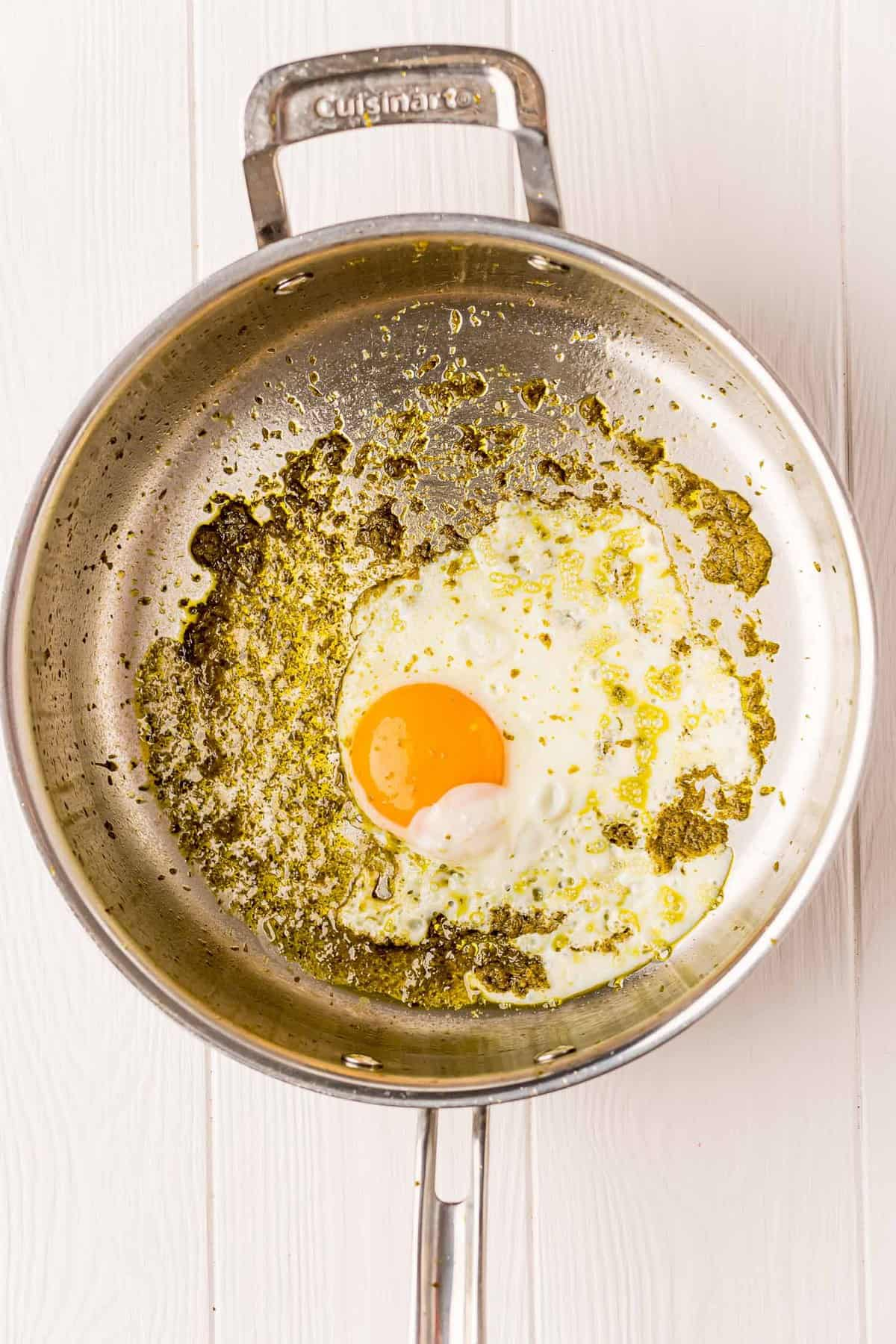 Egg in frying pan with pesto.