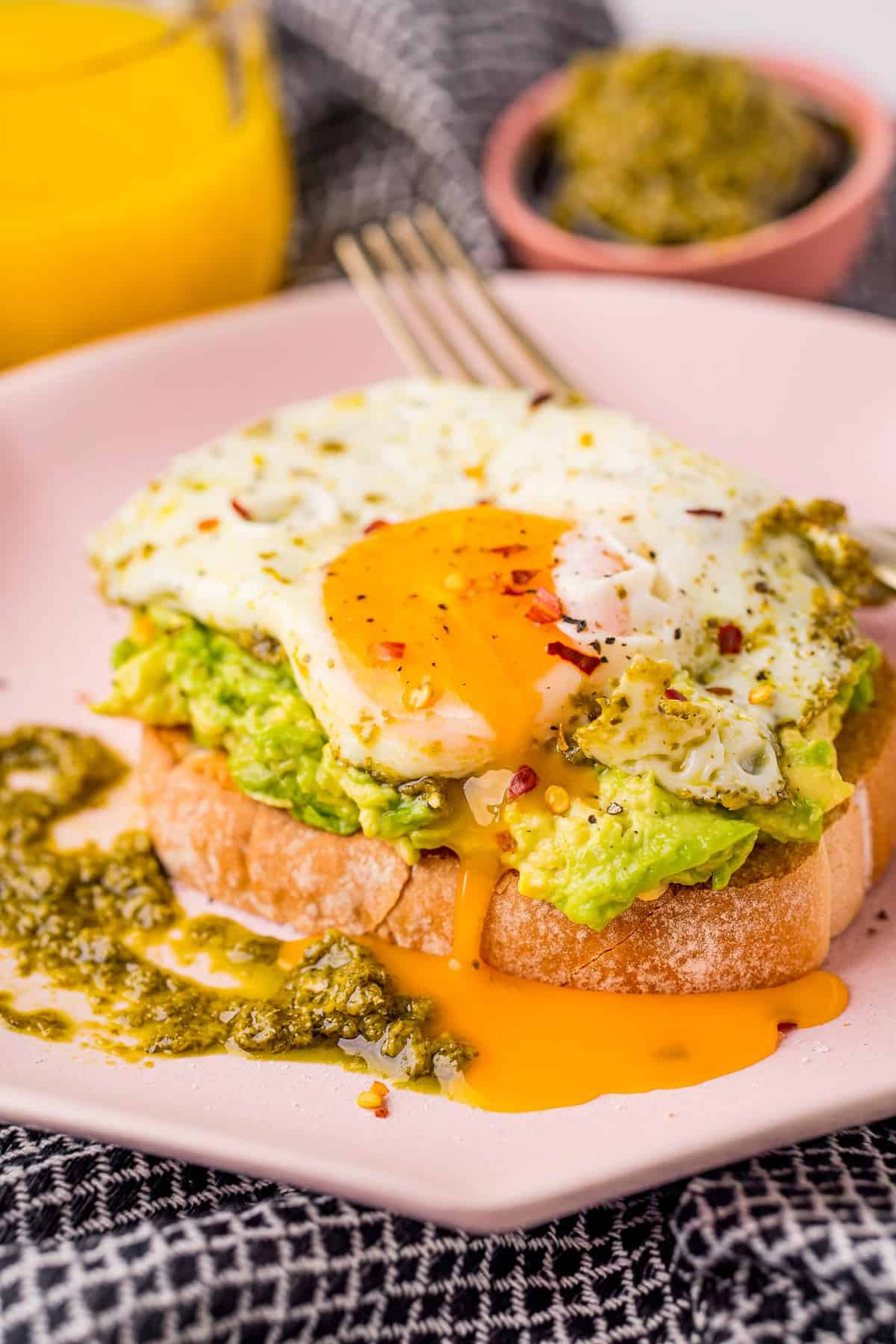Avocado toast topped with a runny egg.
