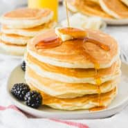 Syrup being poured on a stack of fluffy pancakes.