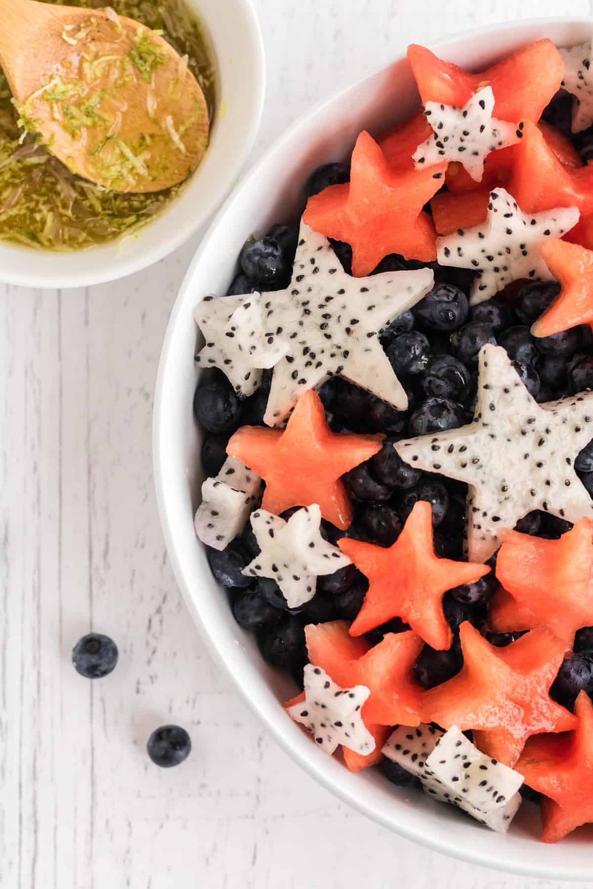 Close up view of fruit salad with watermelon and dragon fruit cut into star shapes.