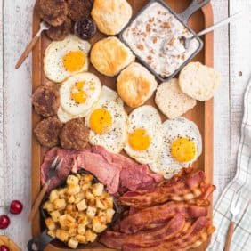 Overhead view of meat, eggs, sausage, potatoes, and biscuits on a large wooden tray.