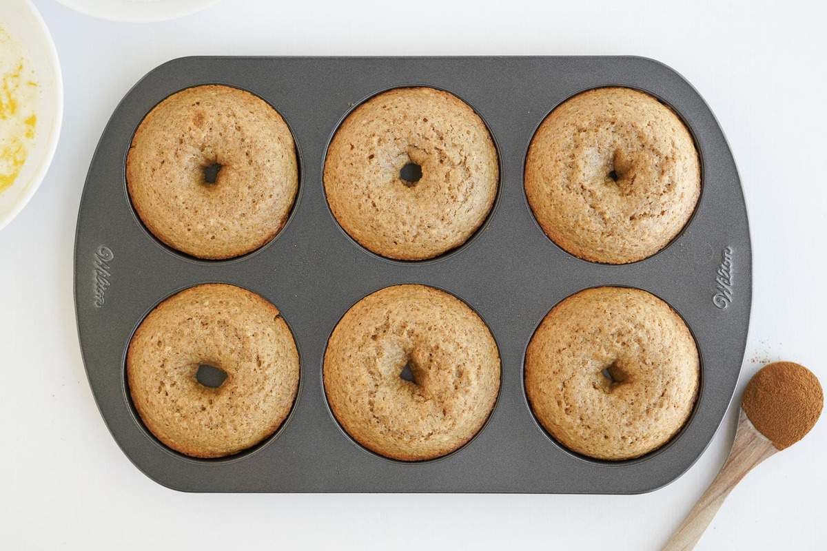 Baked donuts still in a donut pan.