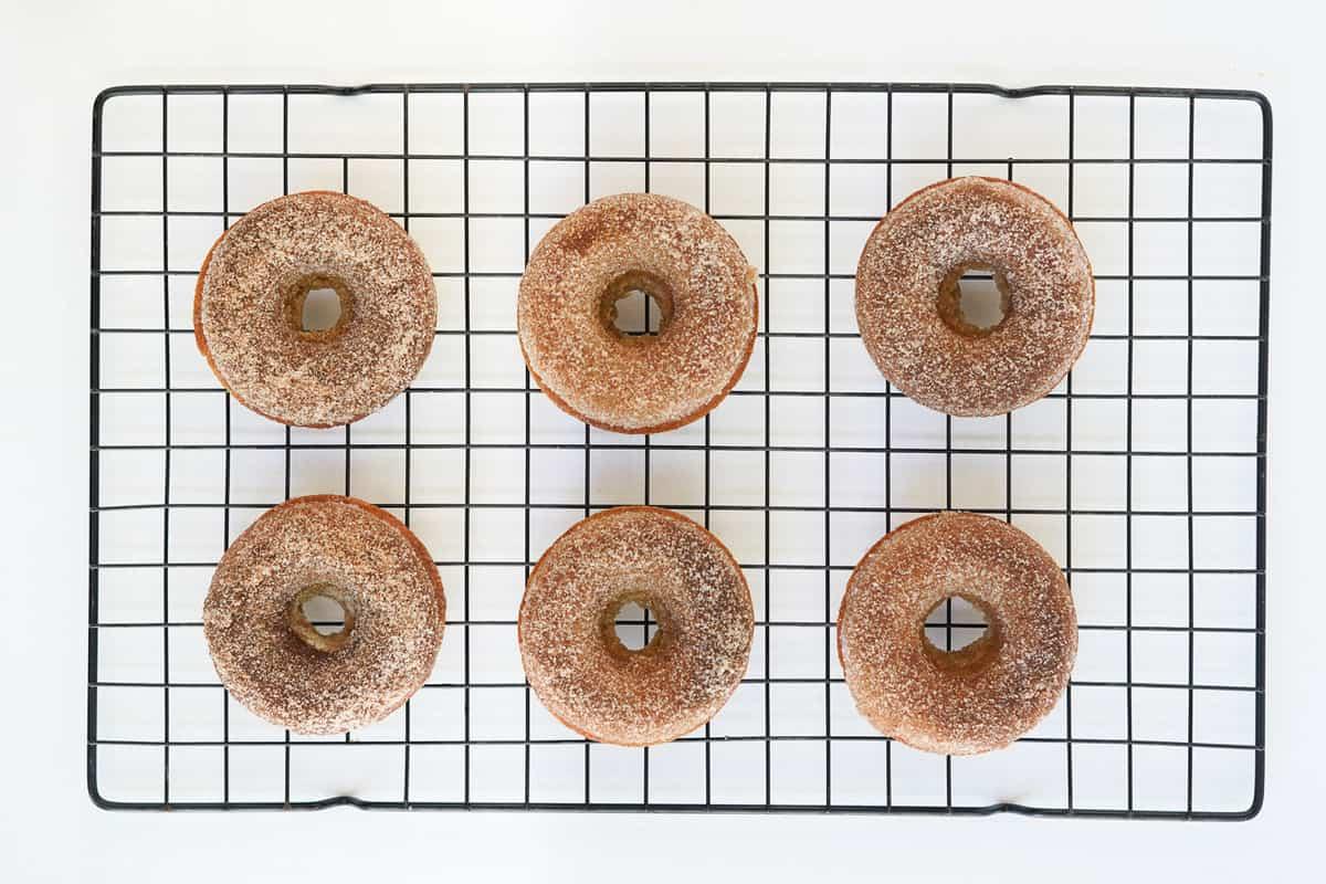Apple cider donuts on a cooling rack.