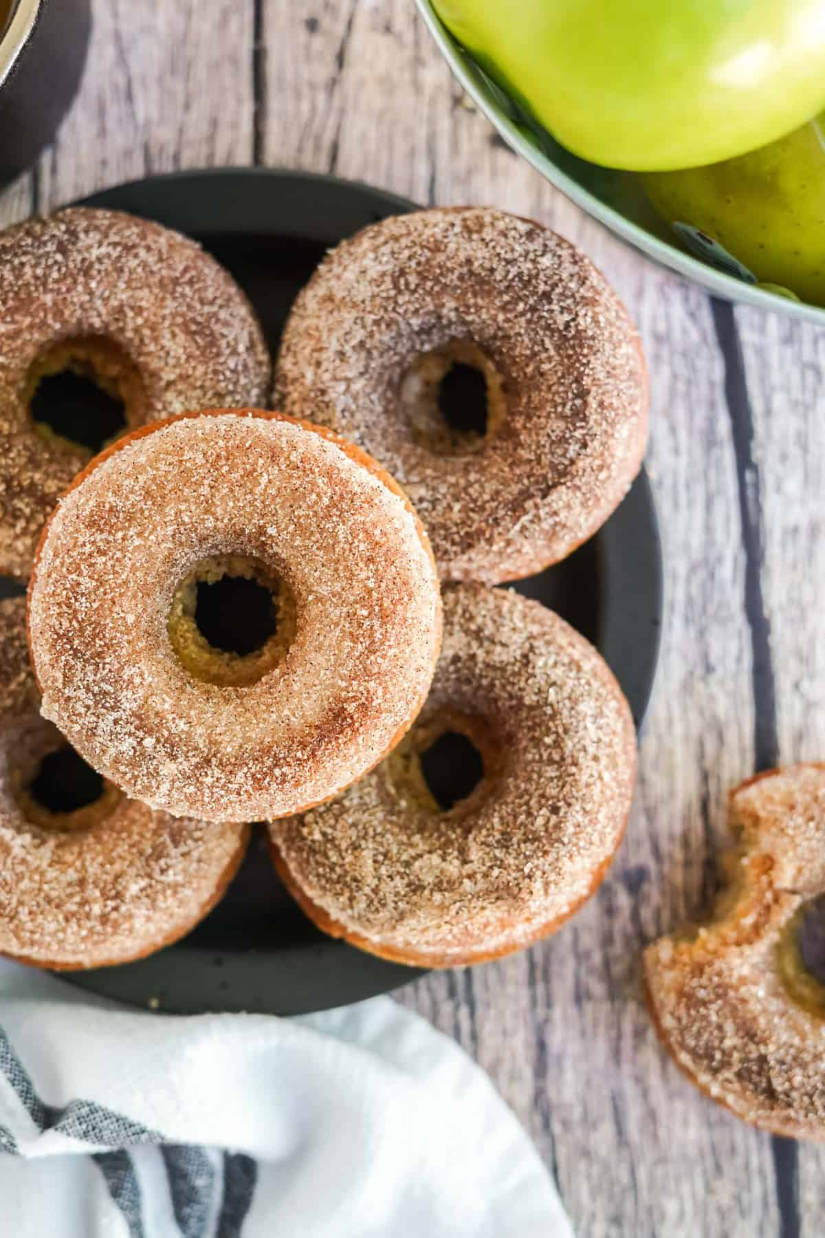 Overhead view of 5 cinnamon sugar dusted donuts on a black plate.