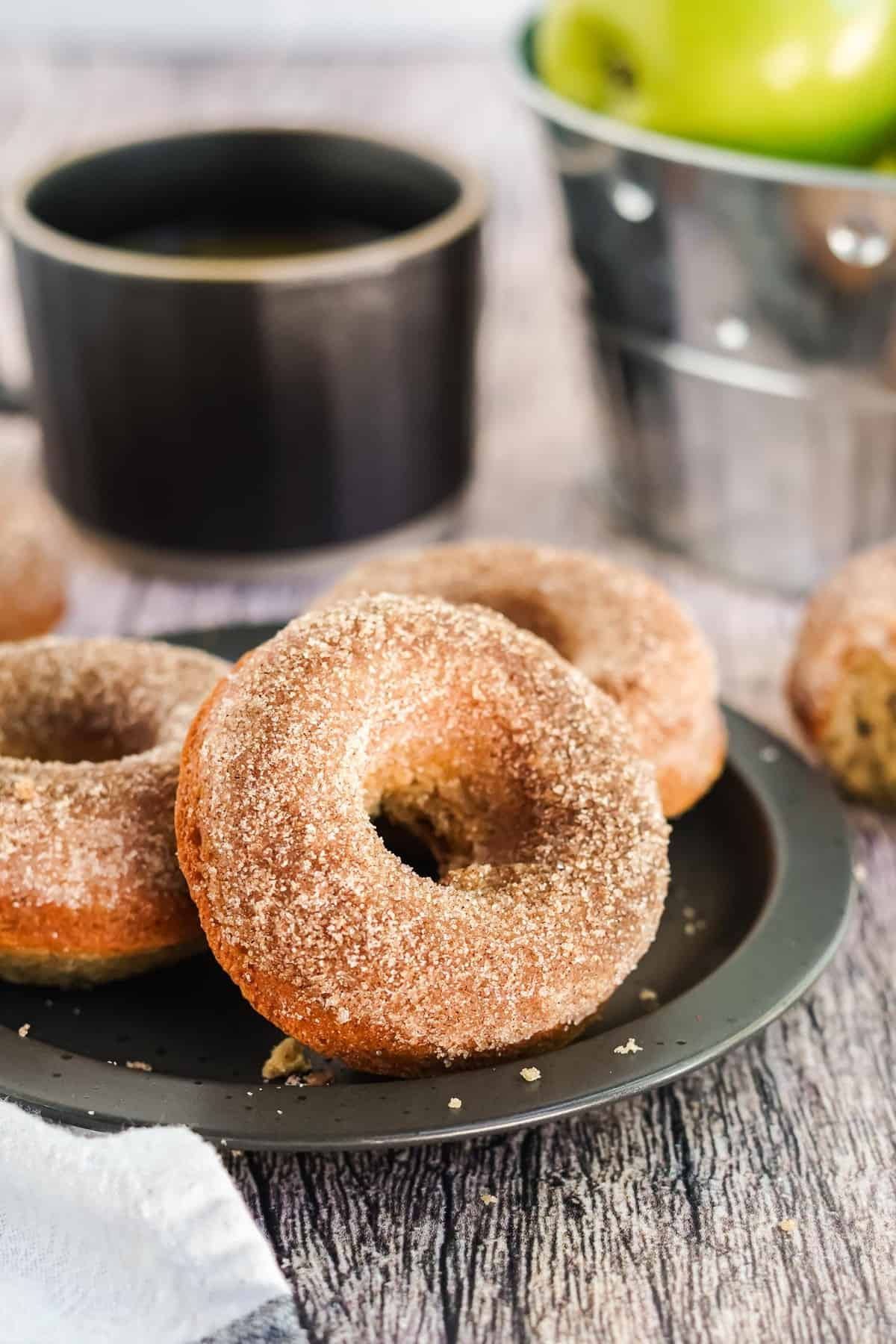 Donuts on a black plate with coffee in the background.