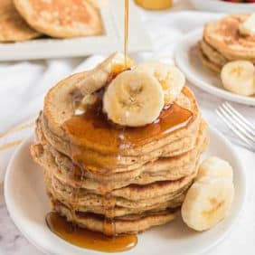 Pancakes with sliced bananas and syrup being poured on top.