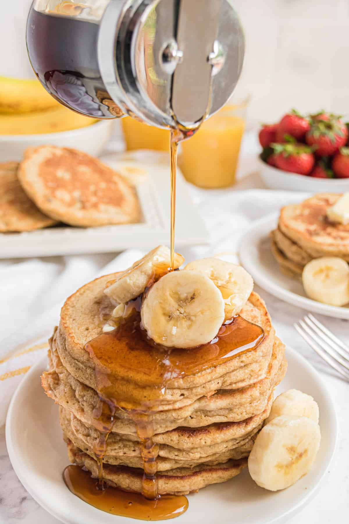 Stack of pancakes with sliced bananas, syrup being poured on top.