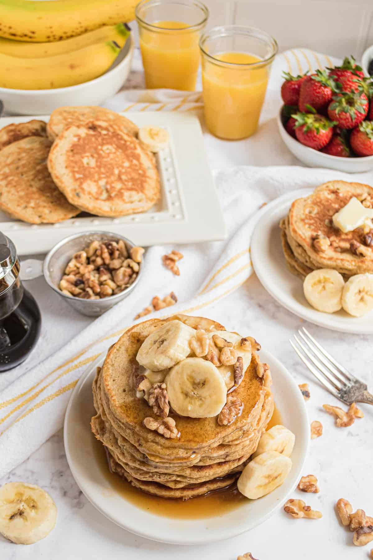 Multiple plates of banana bread pancakes topped with walnuts and sliced bananas.