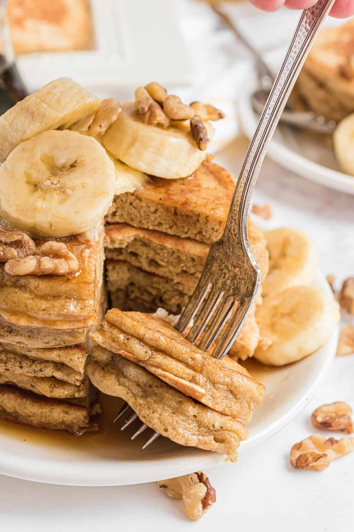 A fork taking part of a stack of banana pancakes.