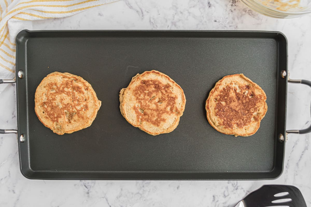 Cooked pancakes on a black griddle.
