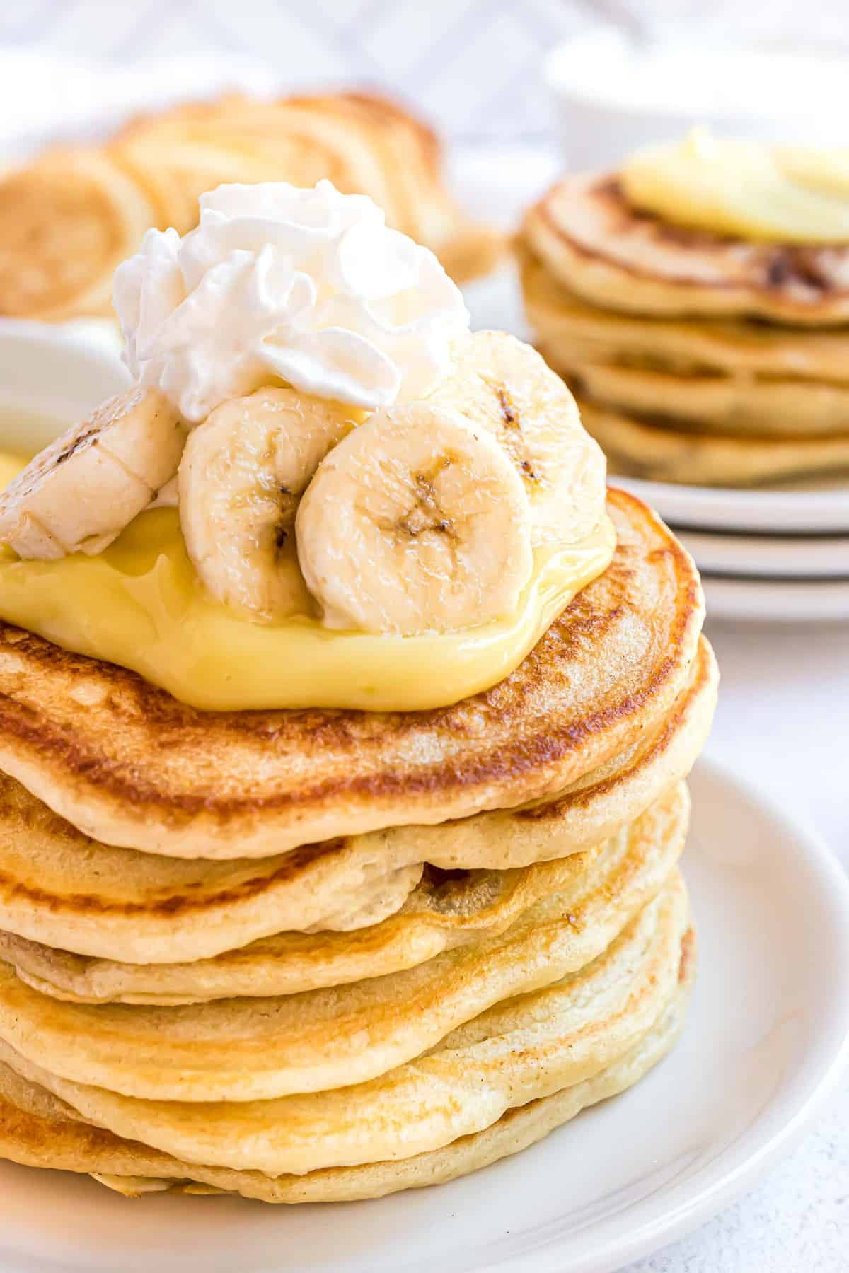 Close up of pancake stack topped with pudding, whipped cream, and bananas.