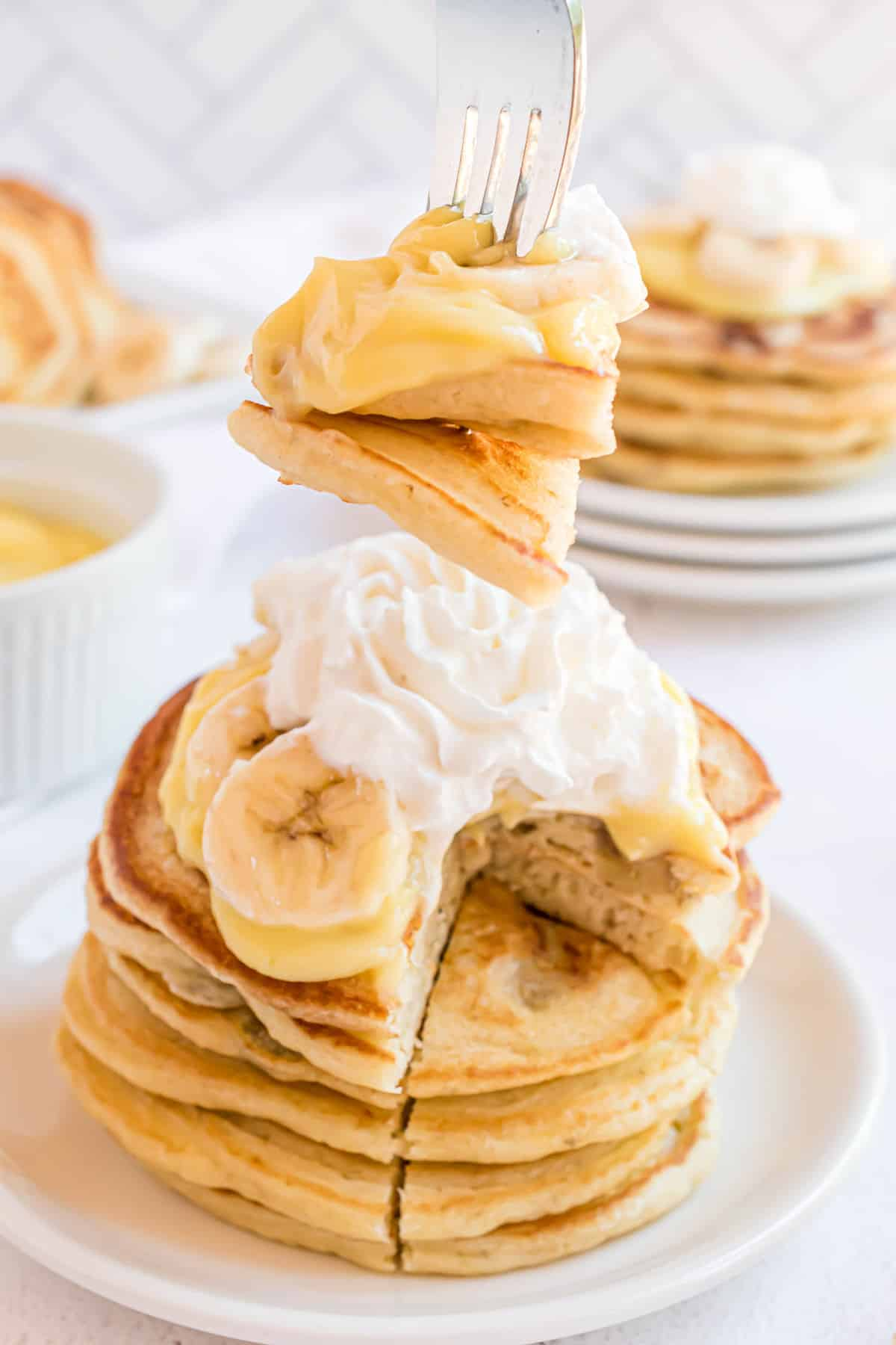 Banana pancakes on a fork, with a stack behind them.