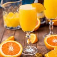 Orange drink in a stemmed glass made with beer and orange juice, topped with orange wedge.