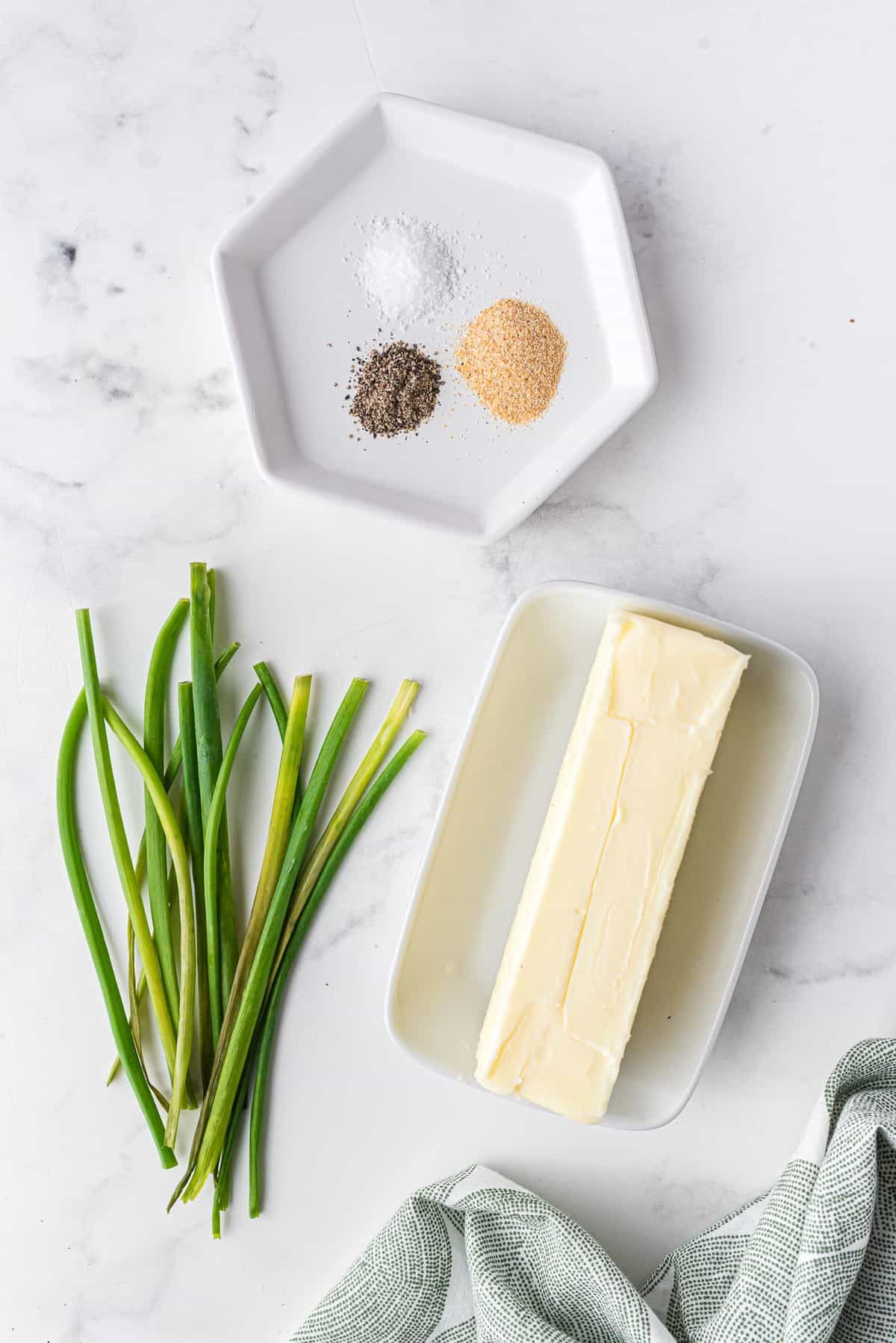 Overhead view of a stick of butter, chives, and assorted seasonings.