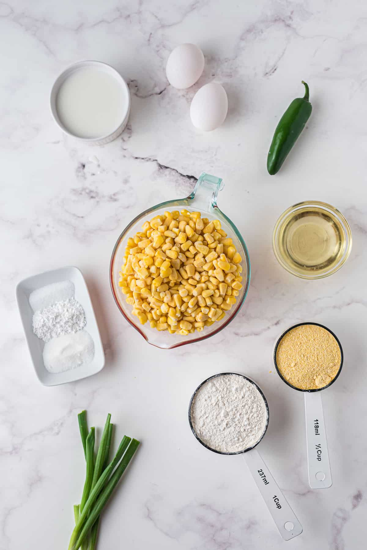 Overhead view of ingredients including corn kernels, green onion, jalapeno, egg.