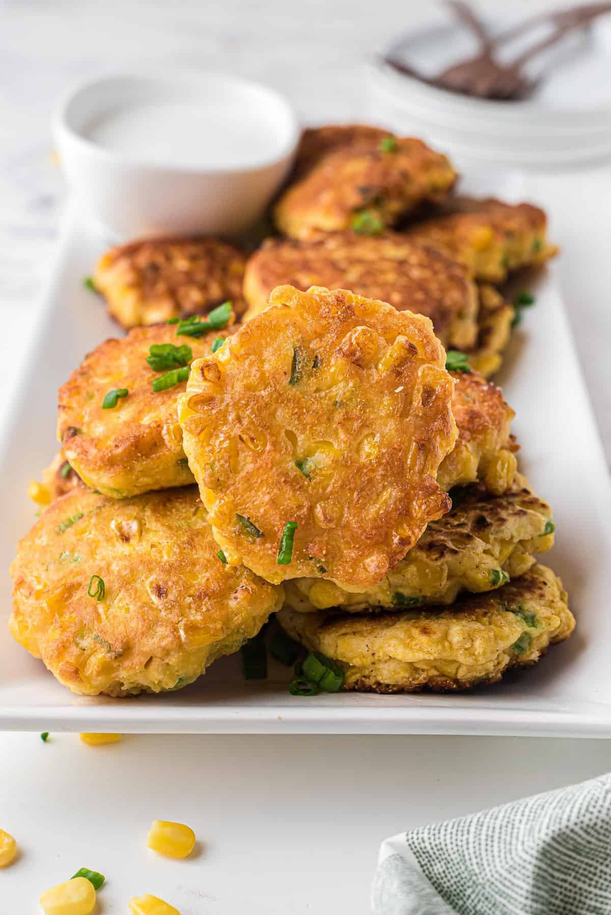 Corn fritters piled high on a white rectangular plate.