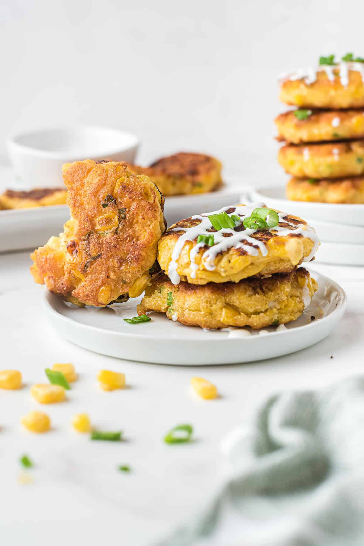 Corn fritters on a plate with sour cream and green onions.